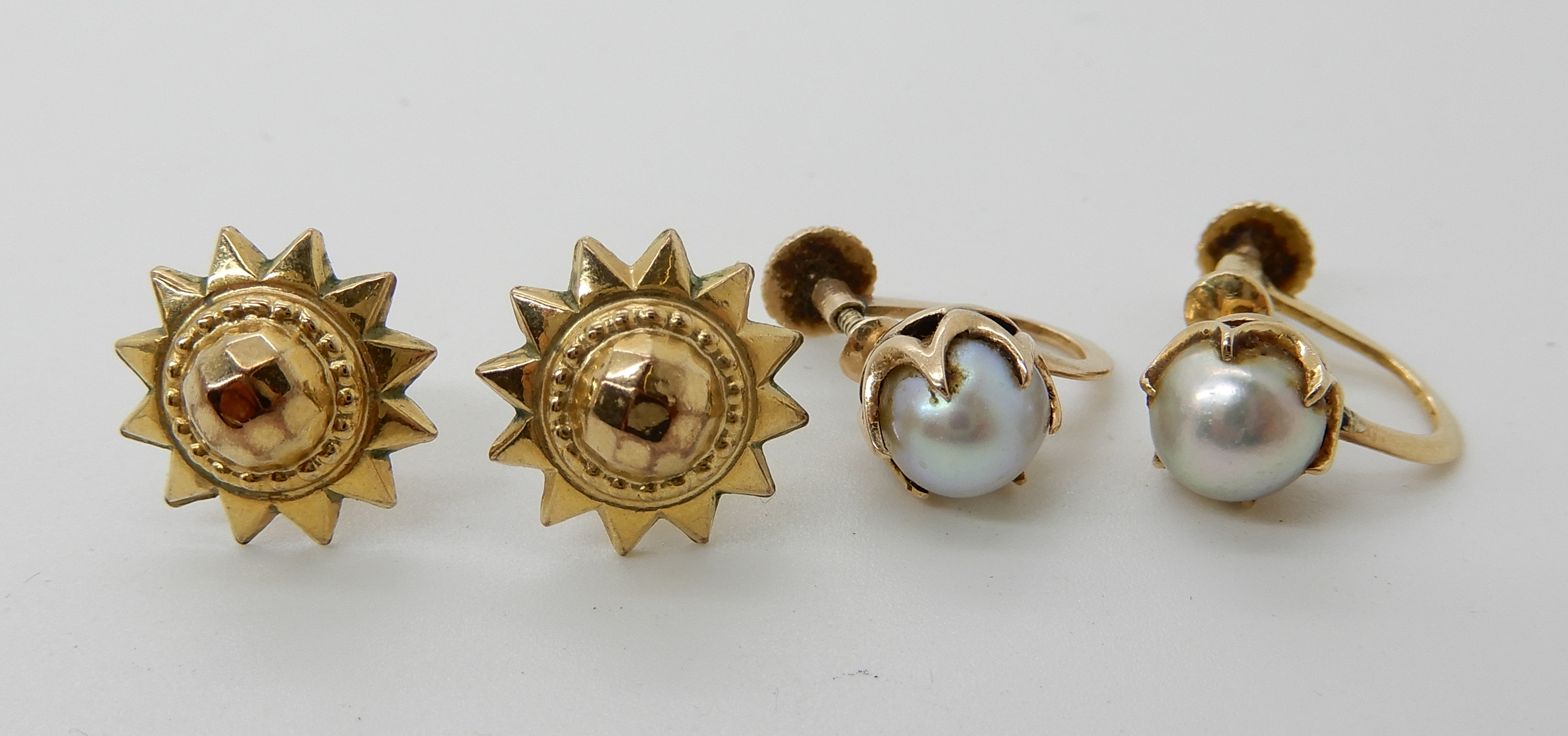 Lot 52 - A pair of 18ct mounted pearl earrings with screw backs and a pair of 9ct gold star earrings weight