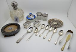 A lot comprising a silver topped scent bottle, a silver and enamel lidded talcum jar, silver mounted