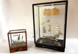 A lot comprising two Chinese white metal model ships in glass cases, one an armed junk the other a