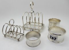A lot comprising two silver toastracks, Birmingham marks and three silver napkin rings, assorted