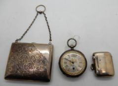 A lot comprising a white metal purse, a silver vesta and a silver cased pocket watch Condition