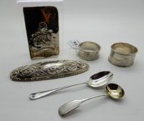 A lot comprising two silver napkin rings, two spoons, a jar lid and a part book cover Condition