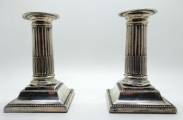 A pair of silver candlesticks, Sheffield 1913, with ribbed stems and beaded border, 12.7cm high,