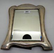 A silver mounted mirror, rubbed Birmingham marks, 30cm x 24cm, glass 20.3 cm x 15.3cm, damaged in
