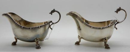 A pair of silver sauceboats, Birmingham 1937, with Celtic decoration, the scrolling handle