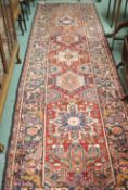 A red ground Karejeh runner with five central lozenges, 356cm x 104cm Condition Report: Available