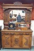 An Arts and Crafts oak sideboard with mirror back and carved panels and drawers, 220cm high x