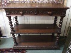 A Victorian carved oak three tier buffet with two drawers with mask handles, 104cm high x 115cm wide