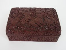 A CHINESE CINNABAR BOX AND COVER carved with kylin with precious objects and ribbons, above