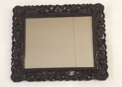 A CHINESE HARDWOOD WALL MIRROR the pierced frame carved with dragons chasing the flaming pearl of