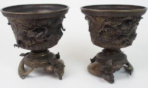 A PAIR OF CHINESE BRONZE JARDINIERES ON STANDS cast with dragons on a raging sea, beneath key