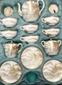 A SATSUMA CASED TEA SET painted with female figures before rivers in a mountainous landscape,