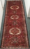 A red ground Karejeh runner with stylised animals and geometric designs, 315cm x 109cm Condition