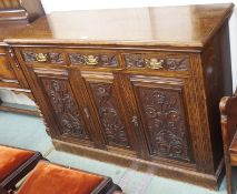 An oak sideboard with three carved drawers over two doors, 100cm high x 137cm wide x 50cm high
