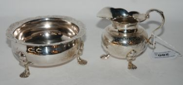 A white metal cream and sugar with engraved decoration (2) Condition Report: Available upon request