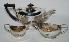 A bachelor's three piece silver tea service, Birmingham 1927, oval with half ribbed body, 329gms