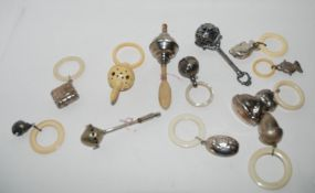 A lot comprising fourteen assorted white metal baby rattles, a plastic one and three baby whistles