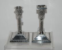 A pair of silver candlesticks, Sheffield 1966 with acanthus decorated sconce on barley twist stem