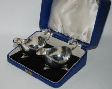 A cased pair of silver sauceboats, Birmingham 1936, with Celtic decorated borders, the open
