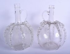 AN UNUSUAL PAIR OF ANTIQUE CONTINENTAL GLASS JUGS of bulbous form with rippled bodies. 24.5 cm high