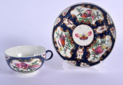 18th c. Worcester teacup and saucer painted with birds in a gilt mirror shaped panel on a blue scale