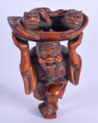 AN EARLY 20TH CENTURY JAPANESE MEIJI PERIOD CARVED BOXWOOD NETSUKE modelled as a male holding aloft