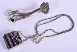 A SILVER PURSE and a silver hand brooch. Largest 6.5 cm wide. (2)