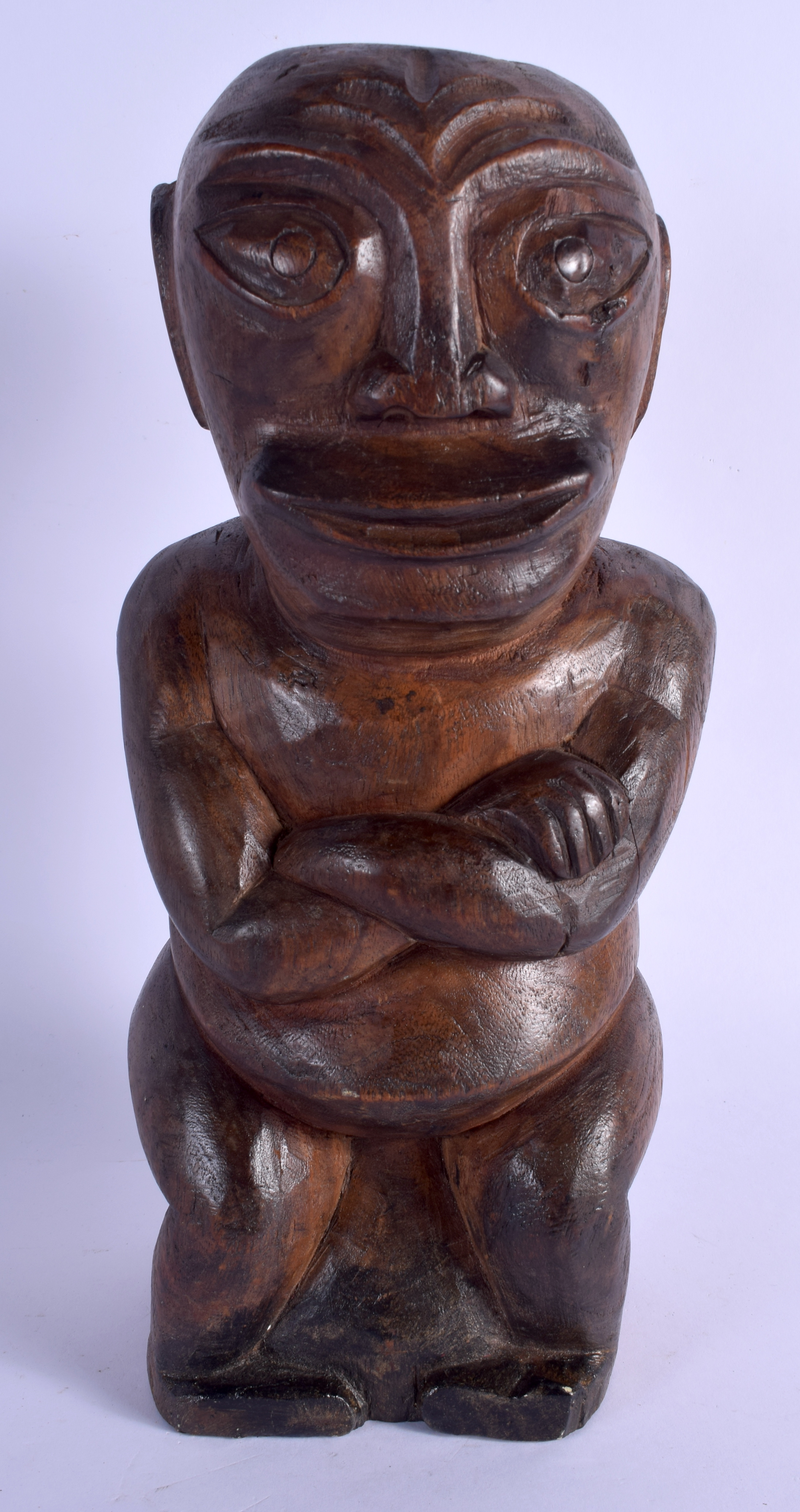 A SOUTH PACIFIC CARVED TRIBAL SEATED FIGURE possibly from Tahiti or Marquesas Islands. 33 cm high.