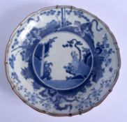 AN EARLY 18TH CENTURY JAPANESE EDO PERIOD BLUE AND WHITE SCALLOPED DISH painted with immortals. 30 c