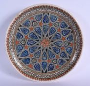 A MIDDLE EASTERN TURKISH KUTAHYA POTTERY DISH painted with star shaped flowers. 30 cm diameter.