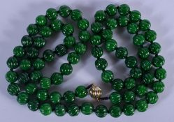 AN 18CT GOLD CHINESE CARVED JADEITE NECKLACE. 104 cm long, each bead 0.7 cm wide.