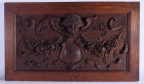 AN ANTIQUE CONTINENTAL CARVED WOOD PLAQUE with central EF monogram. 65 cm x 36 cm.
