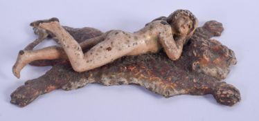 A COLD PAINTED BRONZE FIGURE OF A NUDE LADY modelled upon a tiger skin rug. 12 cm x 6 cm.
