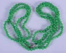 AN 18CT GOLD CHINESE CARVED JADEITE NECKLACE. 140 cm long, each bead 0.3 cm wide.