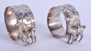 A PAIR OF ART DECO WHITE METAL CAMEL NAPKIN RINGS. 4 cm x 3 cm.