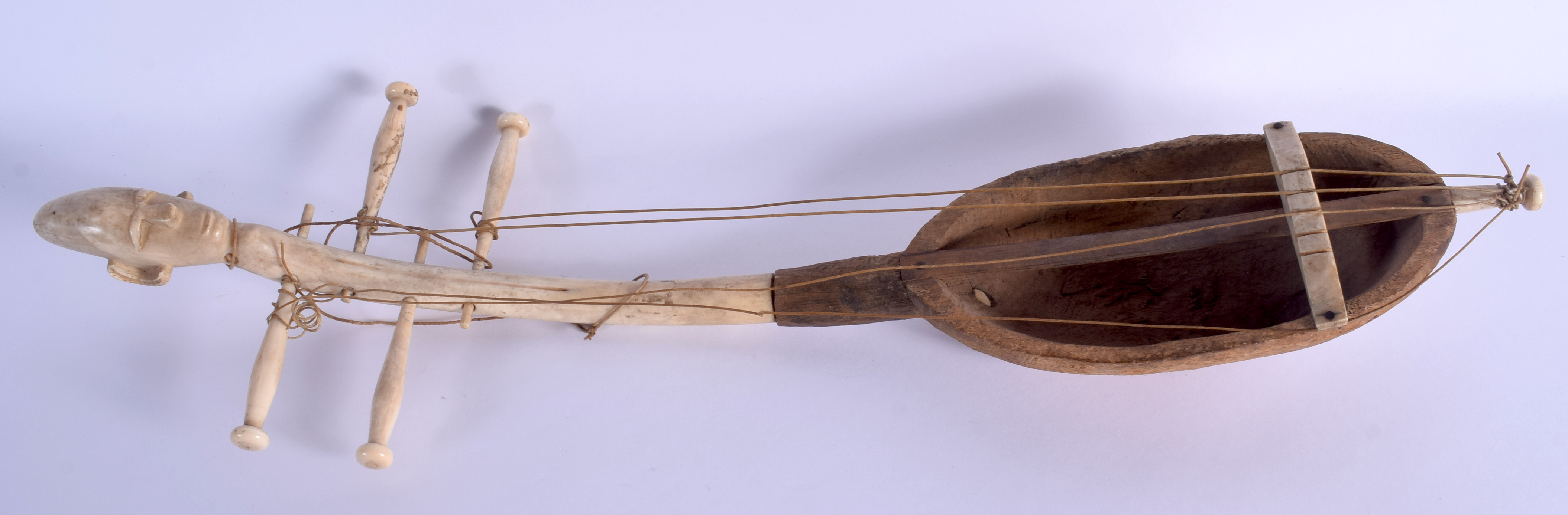 AN EARLY 20TH CENTURY AFRICAN CARVED IVORY AND WOOD INSTRUMENT of figural form. 54 cm long.