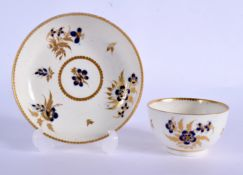 18th c. Worcester teabowl and saucer painted with blue flowers and highlighted with gilded leaves un