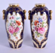 English porcelain fine pair of urn shaped vases with ring handled lavishly painted with flowers surr