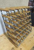 A wine rack of wood and metal construction, unusually sloped by design (Est. plus 21% premium inc.