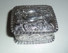 AN EARLY 20TH CENTURY SILVER PILL BOX, decorated to the body with repoussé detail having floral