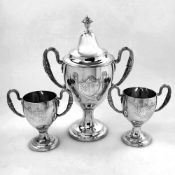 AN 18TH CENTURY IRISH SILVER SET OF TROPHY / CUPS, the larger with lid, Dublin, 1786, each with a