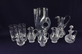 A collection of glass jugs, to include one in the shape of a leather jug, together with two