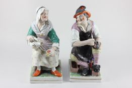 A pair of Staffordshire pottery figures of a cobbler and his wife, 32cm high (a/f)