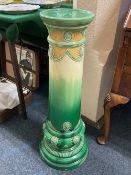 An Art Nouveau Bermantofts faience jardiniere stand, in green and yellow glaze, marks to