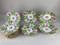 A 19th century porcelain part dessert service, decorated with floral sprays, within green and gilt