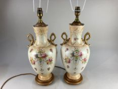 A pair of Victorian baluster vases now as table lamps, decorated with floral sprays on cream