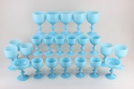 A collection of pale blue milk glass drinking glasses, comprising ten large goblets, eleven small