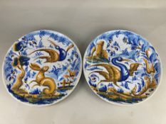 A pair of tin glazed pottery chargers, one decorated with a scene of a hare and a bird by a tree,