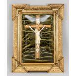 Andachtsbild, um 1900. Jesus am Kreuz (Gips?) vor dunkelgrünem, gerafften Samt. Konvex