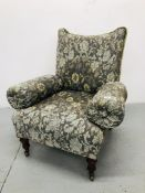 A VICTORIAN UPHOLSTERED ARMCHAIR ON TURNED MAHOGANY LEGS WITH BRASS CASTORS